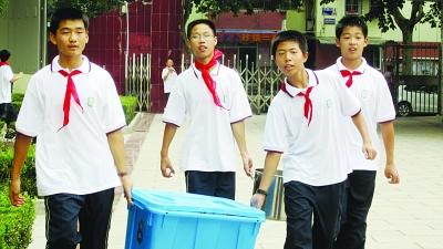 穿共青团路中学校服的学生将餐具抬进教室.-学校新生购买五套校服 图片