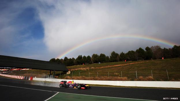 A Formula 1 racing car drives past a rainbow
