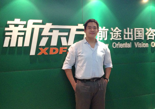Keith Lee在武汉新东方前途出国LOGO前留影