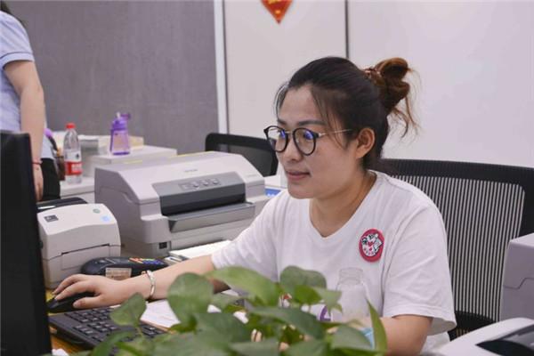 大厅工作人员邢艳艳正在帮家长查询信息