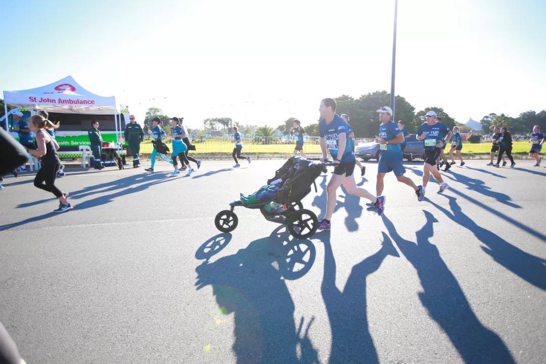 推婴儿车的跑步者